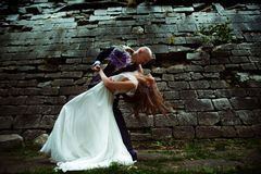 Groom bends bride over and her hair spreads around Stock Image
