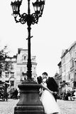 Groom bends bride over standing behind an old lantern on the cit Royalty Free Stock Images