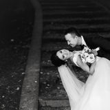 Groom bends bride over standing on the park footsteps covered wi Royalty Free Stock Photography