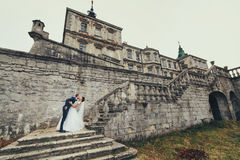 Groom bends bride over standing on the stairs to the old stone c. Astle Stock Image