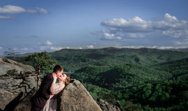 Groom bends bride over the stones while kissing Royalty Free Stock Photos