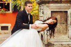 Groom bends brunette bride over standing behind an old pillar Stock Photography