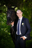 Groom with black horse Stock Images