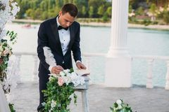 The groom in a black jacket and white shirt with a bow-tie on a wedding day puts a signature near the arch with a lake. On background Stock Photo