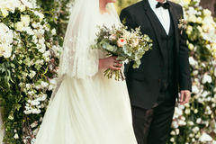 Groom in black suit and bride in white wedding dress with rustic Royalty Free Stock Image