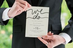 Groom in black suit holding wedding invitation stock images