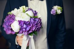 Groom in black suit with wedding bouquet in his hands Royalty Free Stock Photos