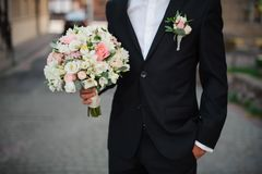 Groom in a black suit holding a gentle wedding bouquet. Groom in a black suit and a white shirt holding a gentle wedding bouquet Stock Images