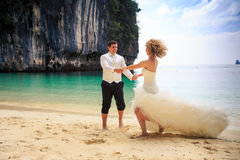 groom blonde bride in fluffy dress join hands swing on beach Stock Photography
