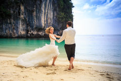 Groom blonde bride in fluffy dress join hands swing on beach Stock Photos