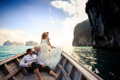 groom blonde bride in fluffy in longtail boat look at islands Royalty Free Stock Images