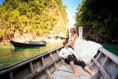 groom blonde bride in fluffy sit on nose of longtail boat Stock Photography