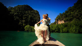 Groom blonde bride in fluffy stand on nose of longtail boat. Groom and blonde curly bride in fluffy wedding dress stand on nose of longtail boat against azure stock photos