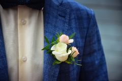 Groom in blue checkered suit with a white and pale pink rose boutonniere. Close up stock photography