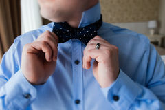 The groom in blue shirt holding a bow tie in his hands. The groom in a blue shirt holding a bow tie in his hands Royalty Free Stock Photography