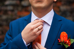 The groom in a blue suit adjusts his orange tie Stock Photos