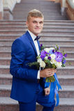 The groom in a blue suit with bouquet. The groom in a blue suit with a bouquet on the steps royalty free stock image