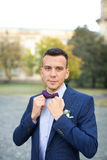 The groom in a blue suit and bow tie posing in the photo. Groom in blue suit with atlas bow Royalty Free Stock Photography