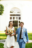 Groom in blue suit and a bride in a white dress walking in the m Stock Photography