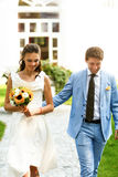 Groom in blue suit and a bride in a white dress walking in the m Royalty Free Stock Photos