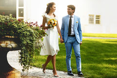 Groom in blue suit and a bride in a white dress walking in the m Stock Image