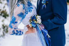 Groom in a blue suit and bride in white in the mountains Carpathians. Groom in a blue suit and bride in white, embroidered with blue pattern, dress on a stock photography