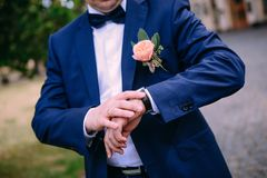Groom wedding costume watch butane outside. Groom in a blue suit with a butanier looks at the clock waiting for the bride Stock Images