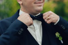 Groom in blue suit fixes his bow tie stock photos