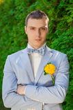 The groom in a blue suit. Gorgeous brunette bride putting on boutonniere on the blue suit of groom royalty free stock image