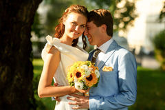 Groom in blue suit holding a bride in a white dress under tree Royalty Free Stock Photography