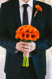Groom in blue suit holding wedding bouquet of flowers in hands Royalty Free Stock Photography