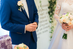 Groom in blue suit holding wedding ring before put it on bride's finger Royalty Free Stock Images