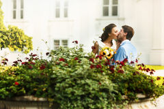 Groom in blue suit kissing a bride in a white dress in the midst Stock Photos