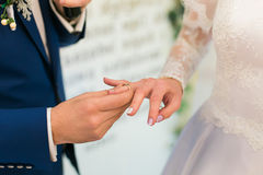 Groom in blue suit putting a wedding ring on bride's finger. Groom putting a wedding ring on bride's finger royalty free stock photos