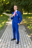 Groom in a blue suit standing in the alley. Portrait of the bride in the park Stock Image