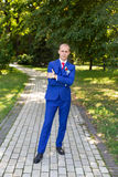 Groom in a blue suit standing in the alley. Portrait of the bride in the park Stock Images