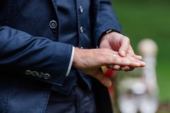 Groom in blue suit touches gold wedding ring on finger.  Stock Image