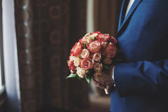 Groom in blue suit with wedding bouquet, waiting. Marriage concept. Groom in blue suit with wedding bouquet of roses, waiting. Marriage concept Royalty Free Stock Images