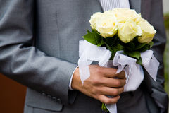 The groom with a bouquet. Groom holding yellow bouquet is jacket stock photos