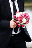 The groom with a bouquet. Groom holding yellow bouquet is jacket royalty free stock image