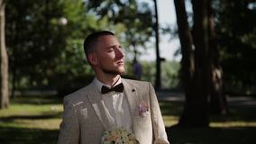 Groom with a bouquet in the city park. Groom with a bouquet in the city park stock footage