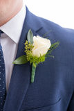 Groom Boutineer on Navy Suit Jacket. Groom boutineer pinned onto his navy suit jacket on his wedding day Royalty Free Stock Images