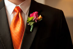 Groom and Boutonniere. Groom waiting for ceremony dressed in tux, tie and boutonniere - corsage Royalty Free Stock Image