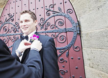 Groom with boutonniere. A smiling groom having his boutonniere put on before his wedding stock images