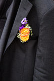 Groom boutonniere on jacket. Orange roses with babys breath in groom boutonniere pinned to black jacket stock images