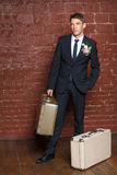 Groom is a brick wall with suitcases Stock Photos
