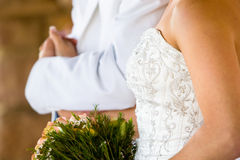 Groom and bride. A horizontal photo of a caucasian bride and groom holding hands during a wedding reception Stock Image