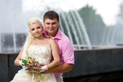 Groom and the bride against a fountain. Royalty Free Stock Photos