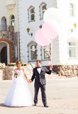 Groom  and bride  with balloons  on  a city Stock Photo