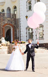 Groom  and bride  with balloons  on  a city Royalty Free Stock Photos